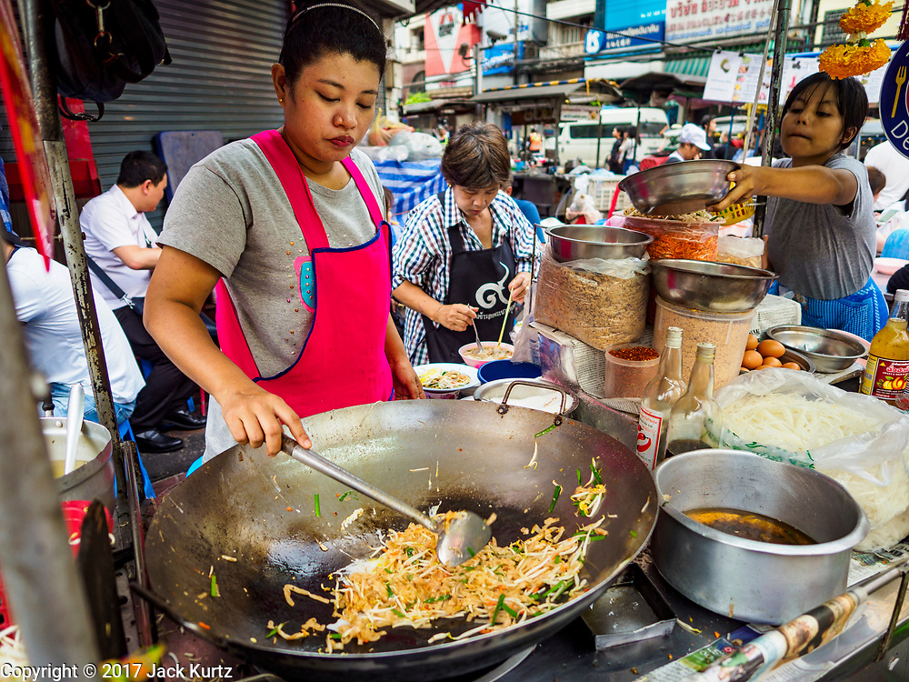 """18 MAY 2017 - BANGKOK, THAILAND:   A vendor makes """"phat Thai"""" (also called """"Pad Thai"""") at a street food stall in Bangkok's Chinatown. Phat Thai is fried rice noodles and Thailand's unofficial national dish. City officials in Bangkok have taken steps to rein in street food vendors. The steps were originally reported as a """"ban"""" on street food, but after an uproar in local and international news outlets, city officials said street food vendors wouldn't be banned but would be regulated, undergo health inspections and be restricted to certain hours on major streets. On Yaowarat Road, in the heart of Bangkok's touristy Chinatown, the city has closed some traffic lanes to facilitate the vendors. But in other parts of the city, the vendors have been moved off of major streets and sidewalks.    PHOTO BY JACK KURTZ"""