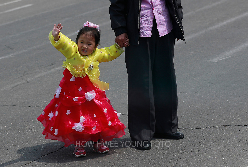 A picture made available on 17 April 2017 of a North Korean girl in traditional costume waving on a road in Pyongyang, North Korea, 16 April 2017. A North Korean missile exploded within seconds of its launch on the east coast on 16 April, South Korean and US officials say as tensions rise in the region over nuclear issues.