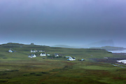 Quaint whitewashed croft cottages in hamlet nestled by the shoreline on a misty grey sky day on the Isle of Skye, Western Isles of Scotland, UK
