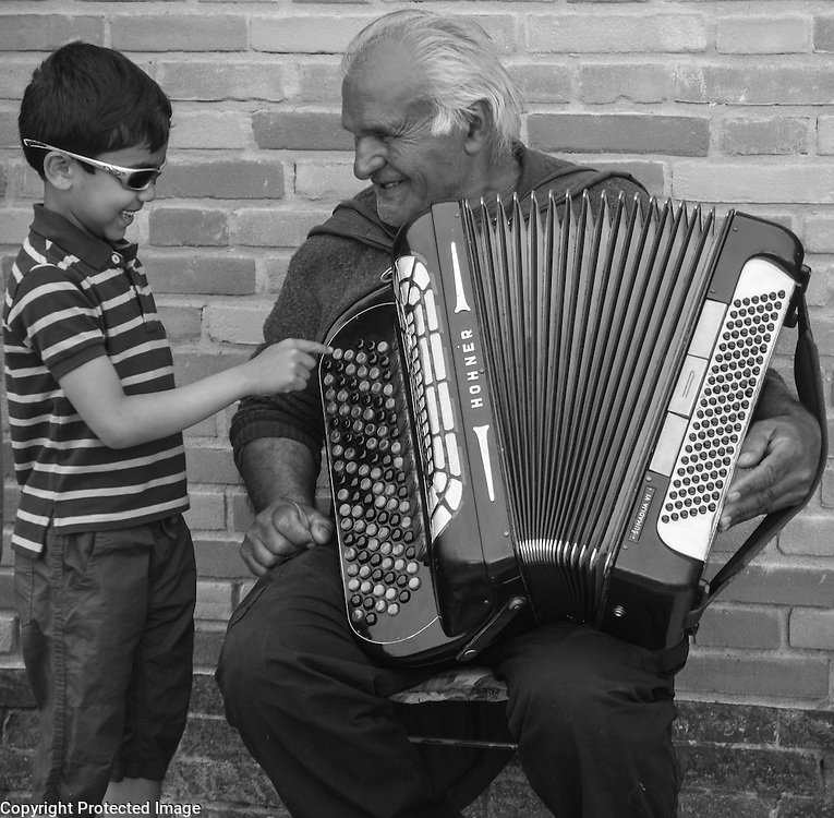 Local musician and child, on Murano Island, Italy