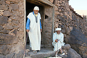 TALIOUINE, MOROCCO - MAY 24TH 2016 - Two locals sit at the entrance of the granary, Taliouine province of Southern Morocco.