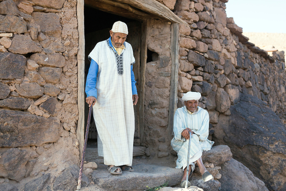 Portrait of the Key Keeper (left) of the Inlatten Granary (Agadir Ait Inlatten) and his friend (right) sitting at the entrance of the granary, Taliouine province of Southern Morocco, 2016-05-24. <br /><br />Notoriously impossible to siege, an agadir is usually placed on top of a mountain or carved into the rocks of dramatic escarpments, strategically located on higher ground beyond settlements, with good vantage points.<br /><br />Traditionally, one security guard known as an &lsquo;amin,&rsquo; stood at the only entrance to each structure and would defend the building from any potential thieves and bandits.<br /><br />The amin was also responsible for holding the keys to the main door and all the chambered storage rooms inside, a tradition which is still kept alive today. This responsibility has always been a well respected role within the local communities surrounding the granaries and each appointed guard serves for a fixed number of years, rotating the privilege among members of the local communities.