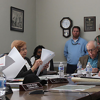 Aberdeen aldermen David Ewing, Carolyn Odom and Jim Buffington look at a road management plan presented by engineer Dustin Dabbs, right, during last week's meeting. The presentation included a discussion about road improvements in the city.