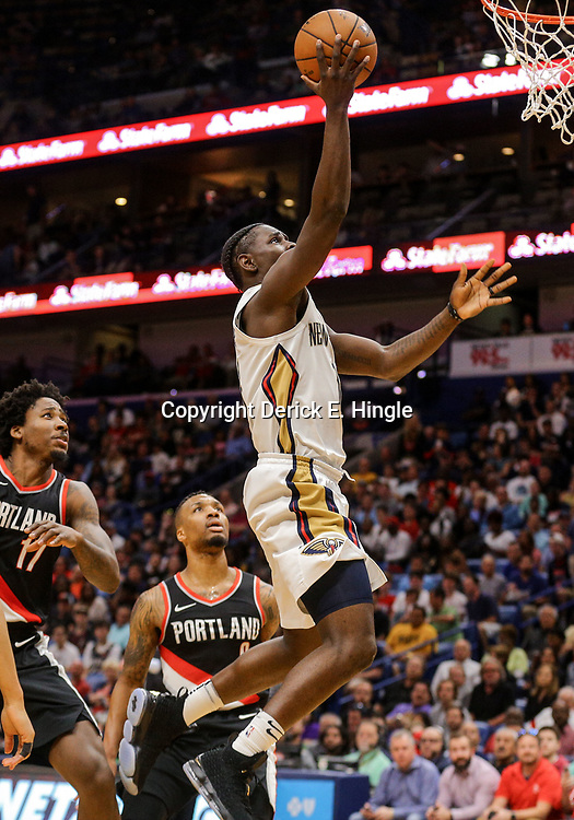 Mar 27, 2018; New Orleans, LA, USA; New Orleans Pelicans guard Jrue Holiday (11) shoots over Portland Trail Blazers guard Damian Lillard (0) and forward Ed Davis (17) during the first quarter at the Smoothie King Center. Mandatory Credit: Derick E. Hingle-USA TODAY Sports