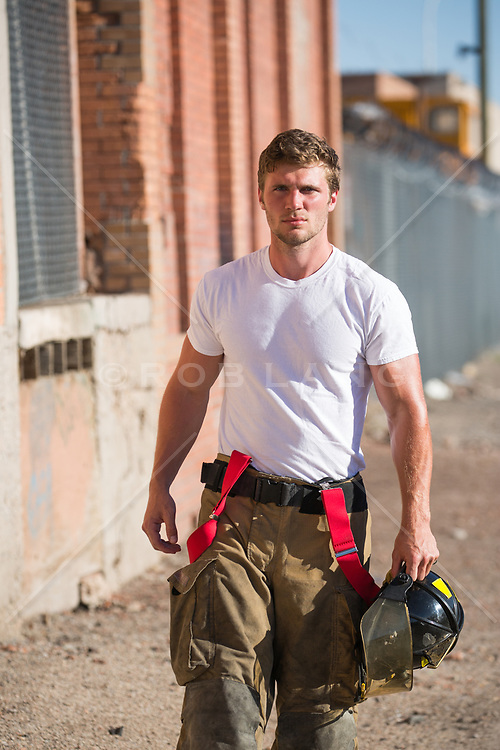 hot fireman outdoors by a brick building