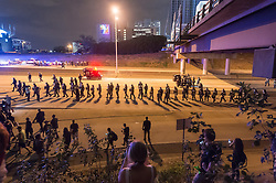 September 22, 2016 - Charlotte, North Carolina, United States of America - September 22, 2016 - Charlotte, NC, USA - Riot police make their way along the highway during a third day of protests in Charlotte, North Carolina on Thursday, Sept. 22, 2016. This is the third day of protests that erupted after a police officer's fatal shooting of an African-American man Tuesday afternoon and the first full day of a declared State of Emergency by the governor. (Credit Image: © Sean Meyers via ZUMA Wire)