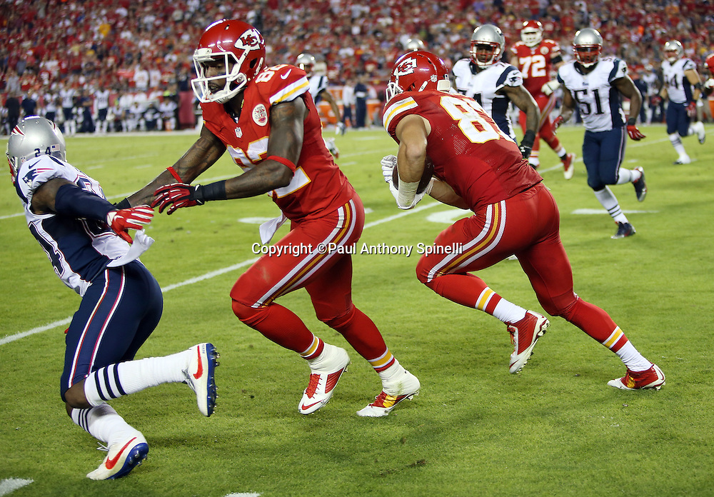 Kansas City Chiefs wide receiver Dwayne Bowe (82) blocks New England Patriots cornerback Darrelle Revis (24) as Kansas City Chiefs tight end Travis Kelce (87) catches a third quarter pass good for a first down during the NFL week 4 regular season football game against the New England Patriots on Monday, September 29, 2014 in Kansas City, Mo. The Chiefs won the game 41-14. ©Paul Anthony Spinelli