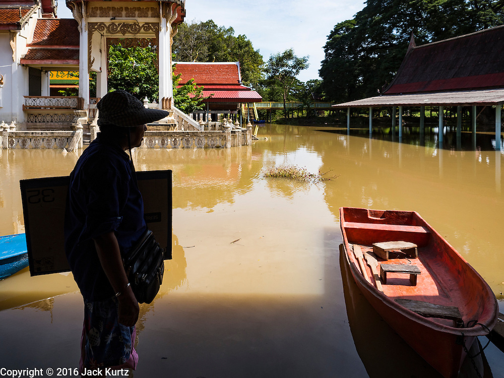 30 SEPTEMBER 2016 - SAI NOI, AYUTTHAYA, THAILAND: A lottery seller waits for a boat to take her home in Sai Noi. The Chao Phraya River, the largest river that runs through central Thailand, has hit flood stage in several areas in Ayutthaya and Ang Thong provinces. Villages along the river are flooded and farms are losing their crops due to the flood. This is the same area that was devastated by floods in 2011, but the floods this year are not expected to be as severe. The floods are being fed by water released from upstream dams. The water is being released to make room for heavy rains expected in October.      PHOTO BY JACK KURTZ
