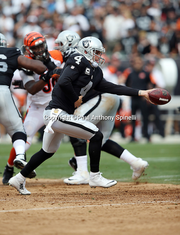 Oakland Raiders quarterback Derek Carr (4) hands off the ball on a running play during the 2015 NFL week 1 regular season football game against the Cincinnati Bengals on Sunday, Sept. 13, 2015 in Oakland, Calif. The Bengals won the game 33-13. (©Paul Anthony Spinelli)
