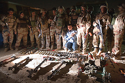 Ahmed Mohammed Ali, also known as Neshuan, is forced to pose for photos with soldiers from Iraqi Army Battalion 222, Mosul, Iraq, Dec. 12, 2005. His capture led them to a cache of weapons consisting of three rocket propelled grenade launchers, two sniper rifles, an anti-tank rocket launcher, a huge pile of ammunition, grenades and rockets. The cache was taken from a van in a parking lot next door to a polling station. Members of the 1st Infantry, 17th Regiment, assisted Iraqi Army Battalion 222, as they planned and executed this raid with the help of an informant. US forces were helping Iraqi forces secure western Mosul in preparation for Iraq's first post-Saddam parliamentary elections. The western sector is home to Mosul's primarily Sunni population, which has been resistant to the American presence in Iraq.