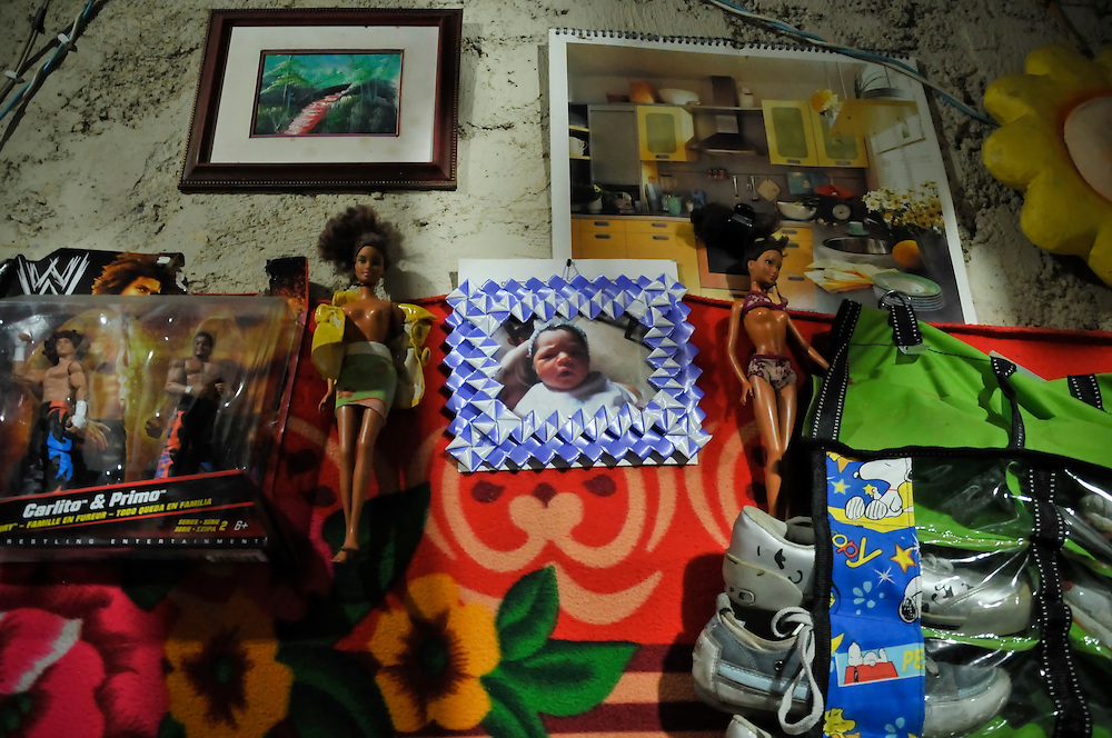 "The wall of a home on the 7th floor of the ""Tower of David"" displays a photograph of a neat and tidy modern kitchen, WWF action figures, Barbie dolls with their shirts unbuttoned, and a photograph of a baby in a handmade frame."