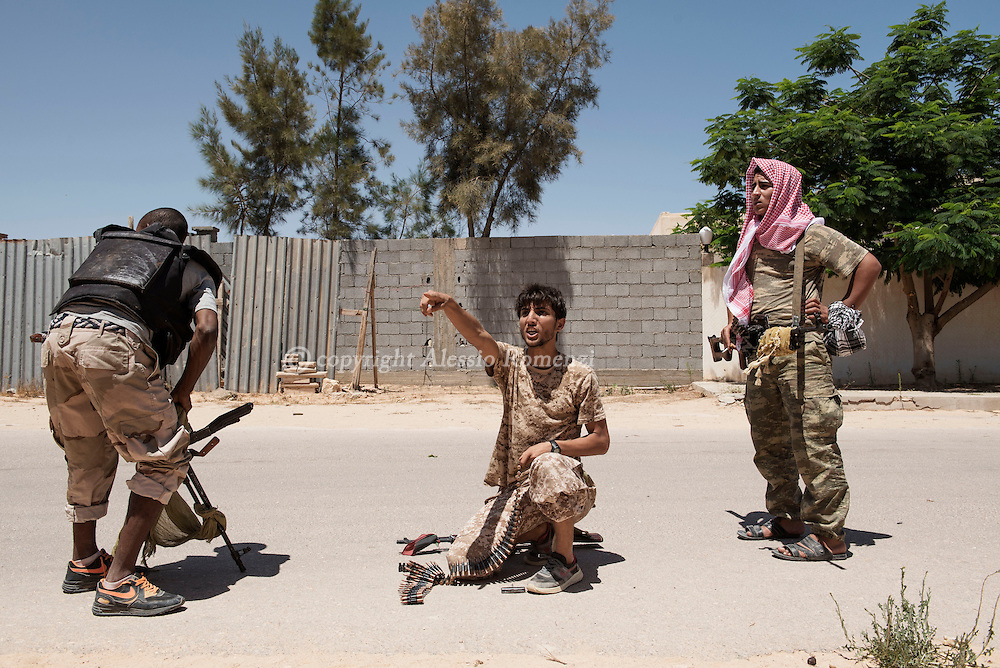 Libya: As they prepare an heavy machine gun, Libya's Government of National Accord's (GNA) fighters take cover from ISIS snipers in 700 neighbourhood in Sirte. Alessio Romenzi