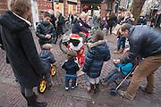 Zwarte Pieten delen strooigoed uit aan het winkelend publiek in Utrecht.<br /> <br /> Zwarte Pieten are giving candies to the children in Utrecht.