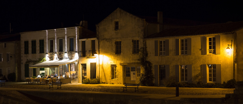 Evening al fresco dining street scene and traditional architecture at St Martin de Re on Ile de Re, France