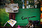 A security guard reads the morning newspaper while on duty outside a grocery store in the Defence Colony market early in the morning on 20th October 2008 in New Delhi, India. With internet still out of reach for 95% of the country and literacy higher than ever, more and more are turning to newspapers and magazines.  Photo : Suzanne Lee