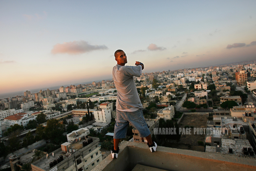 """GAZA CITY, GAZA STRIP - AUGUST 21: Palestinian hip-hop artist of """"DARG"""", Mohammed Antar, stands for a portrait on the edge of a 10-story building overlooking Gaza on August 21, 2009, in Gaza City, Gaza Strip. Hip-hop has grown with popularity throughout Gaza for almost a decade, but as Hamas grows more conservative in an effort to appease a growing number of hardline Islamists, artists such as """"Palestinian Unit"""" and """"Darg"""" are finding it more and more challenging to  propagate their message on war, poverty and civil strife to the youth of Gaza. Their lyrics and behavior on stage is scrutinized by Hamas officials and no performance can be made without prior approval. Many of them have faced repeated harassment due to their western-style  music and appearance. (Photo by Warrick Page)"""