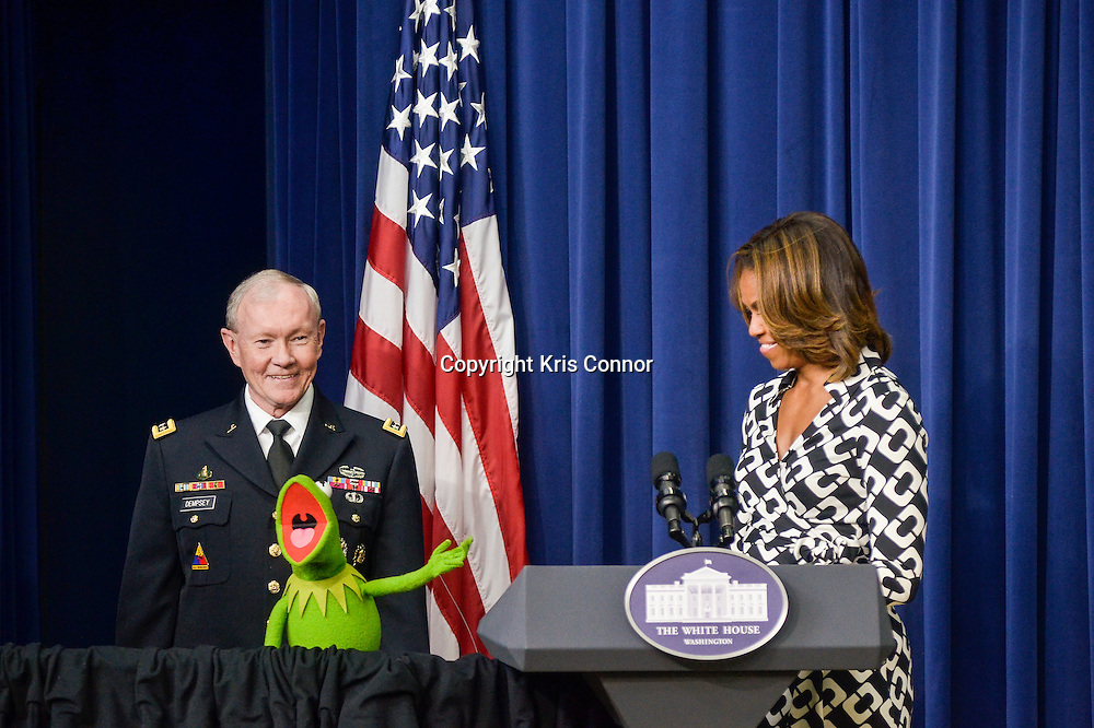 First Lady Michelle Obama with the Chairman of the Joint Chiefs of Staff, General Martin Dempsey and Kermit the Frog deliver remarks during a special screening of Disney's Muppets Most Wanted for a group military children and their families put on by the Joining Forces Initiative at the White House on March 12, 2014 in Washington DC. Photo by Kris Connor/Disney