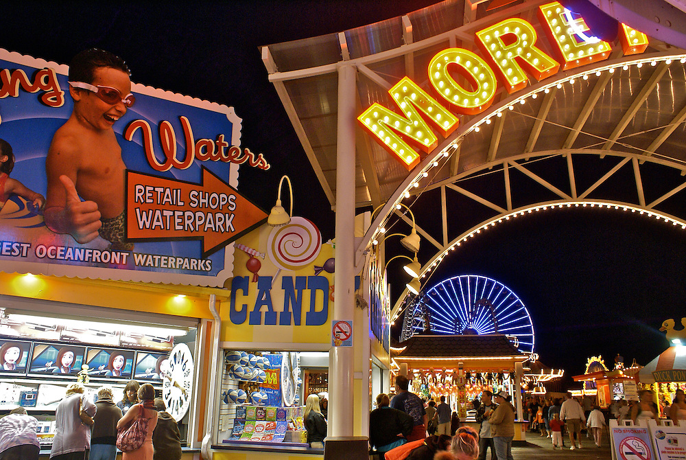 Signs, people and ferris wheel on Wildwood, NJ boardwalk