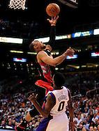 Mar. 23, 2011; Phoenix, AZ, USA; Toronto Raptors guard Jerryd Bayless (5) puts up a basket against the Phoenix Suns guard Aaron Brooks (0) at the US Airways Center. Mandatory Credit: Jennifer Stewart-US PRESSWIRE