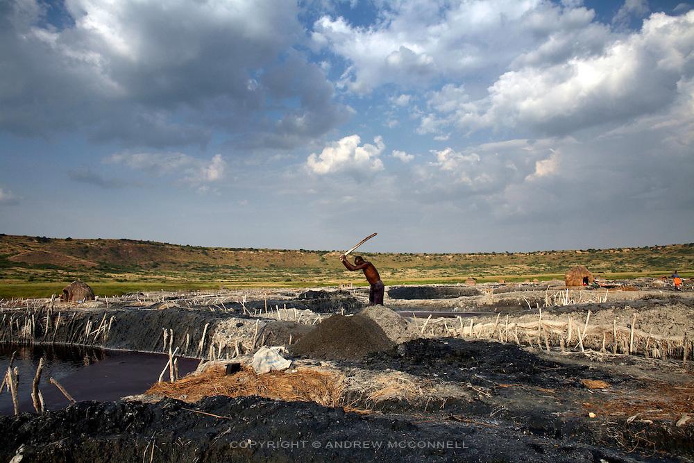 A man beats a salt mound to break up the hardened salt, at Lake Katwe, Uganda.
