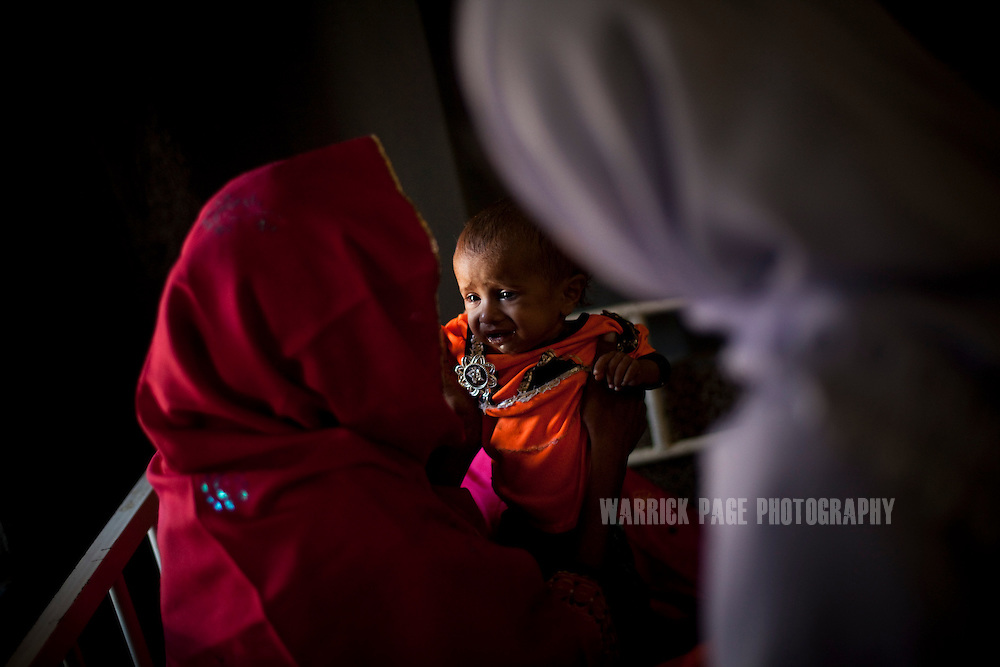 Umeera, 20, rests with her child, Umbreen,14 months, at a nutrition stabilisation centre, on October 14, 2011, in Thatta, Pakistan. Umbreen was born low birth-weight and did not develop a full appetite and needed to be taken to a nutrition stabilisation centre. According to UN reports, hundreds of thousands of children in Pakistan suffer from severe-acute-malnutrition, with 15.1% of children experiencing acute malnutrition. Child malnutrition has breached emergency levels in Pakistan's Sindh province, after monsoon floods devastated the country's poorest region for a second year. Extreme poverty, poor diet and health, exposure to disease, and inadequate sanitation and hygiene annually produce alarming levels of malnutrition amongst children, but the floods have increasingly endangered an already vulnerable population. (Photo by Warrick Page)