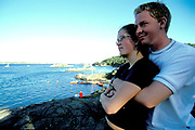 A young couple standing on the shore looking out into the sea. Kristiansands Norway 2000
