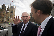 Outside Parliament, the coalition's Business Secretary, Lib-Dem MP Vince Cable crosses St Margaret's Street in Westminster with advisors.