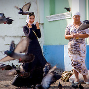 Young woman and grandmother behind flying pigeons (Sergiev Posad, Russian Federation - Aug. 2008) (Image ID: 080821-1414133a)