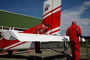 Flugzeugmechaniker bei Reparaturen auf dem Flugplatz Epagny. Mécaniciens en train d'effectuer une réparationde maintien d'un avios à l'aèrodrome d'Epagny, Gruyère, 2009.