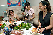 Stephanie, 21, (centre) Sima, 27, (right) and another member of the Freegan community are preparing bread and vegetables at a dinner made entirely with food recovered from dumping sites around the island of Manhattan, New York, NY., on Friday, June 23, 2006. Freegans are a community of people who aims at recovering wasted food, books, clothing, office supplies and other items from the refuse of retail stores, frequently discarded in brand new condition. They recover goods not for profit, but to serve their own immediate needs and to share freely with others. According to a study by a USDA-commissioned study by Dr. Timothy Jones at the University of Arizona, half of all food in the United States is wasted at a cost of $100 billion dollars every year. Yet 4.4 million people in the United States alone are classified by the USDA as hungry. Global estimates place the annual rate of starvation deaths at well over 8 million. The massive waste generated in the process fills landfills and consumes land as new landfills are built. This waste stream also pollutes the environment, damages public health as landfills chemicals leak into the ground, and incinerators spew heavy metals back into the atmosphere. Freegans practice strategies for everyday living based on sharing resources, minimizing the detrimental impact of our consumption, and reducing and recovering waste and independence from the profit-driven economy. They are dismayed by the social and ecological costs of an economic model where only profit is valued, at the expense of the environment. In a society that worships competition and self-interest, Freegans advocate living ethical, free, and happy lives centred around community and the notion that a healthy society must function on interdependence. Freegans also believe that people have a right and responsibility to take back control of their time.