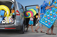 Father and two children (6-11) unloading beach accessories from car