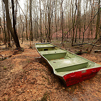 Thomas Wells   BUY AT PHOTOS.DJOURNAL.COM<br /> A lone aluimiun boat rests in the woods hundreds of yards away from Lake Whiteside on Monday following a levee collapse that emptied the lake on Friday.