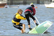Two young boys righting a Laser yacht after capsizing in 18 knots of breeze on the River Hamble. United Kingdom.