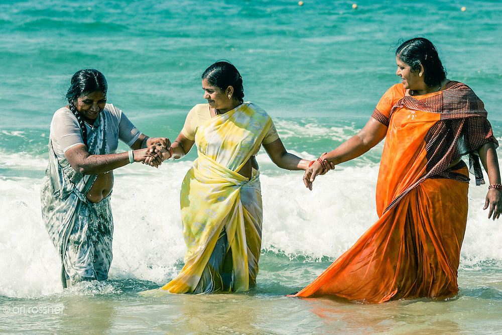 Three women in traditionnal sari outgoing from the water at the beach.