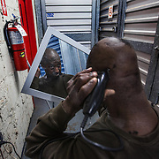 WASHINGTON, DC-OCT14: Michael Evans, 54, uses an electrical outlet to cut his hair in a hallway between storage units at Capital Self-Storage, October 14, 2015, in Washington, DC. Evans who has slept on the streets for years, stores his belongings at the facility, and spends much of his day around his unit. Many of the area homeless have possessions they want to keep safe, just nowhere permanent to live, so they store their belongings at Capital Self-Storage, where an upper-level unit costs $30/month. Some of the homeless patrons also spend their days in their storage units, when shelters are closed during midday hours. The storage facility near 3rd and Florida Avenue in Northeast, Washington, DC, is about to be replaced by a boutique hotel. (Photo by Evelyn Hockstein/For The Washington Post)