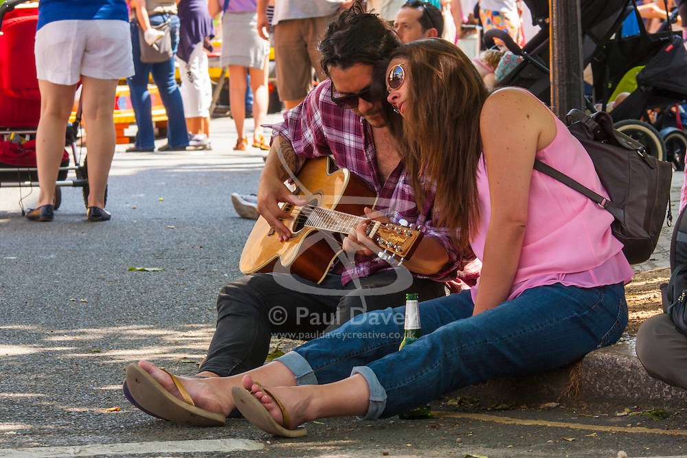 Primrose Hill, London, May 18th 2014. A guitarist plays on the pavement as hundreds of Londoners enjoy the hot sunbshine and dappled shade at the Primrose Hill Fair in London
