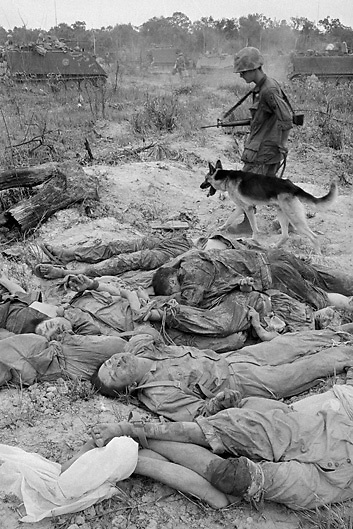 "12 Apr 1968, South Vietnam --- A soldier of the 25th Infantry Division and his scout dog walk past the bodies of more than 50 Viet Cong killed in the ""battle of Good Friday"" 80 miles northwest of Saigon. The infantry division was participating in Operation Complete Victory when their campsite was attacked. --- Image by © Bettmann/CORBIS"