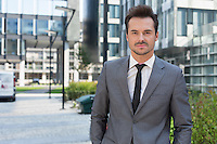Portrait of confident young businessman standing outside office building