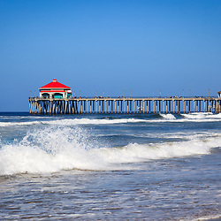 Photo of Huntington Beach Pier. The pier is a registered historic place and has a Ruby's Restaurant at the end. Huntington Beach is a seaside beach city along the Pacific Ocean in Orange County Southern California and is also known as Surf City USA.