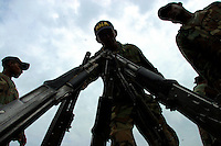 Members of the paramilitary group Bloque Norte, or Northern Block, stack their weapons at a disarmament ceremony in Chimila, in northern Colombia, on March 8, 2006. An estimated 24,000 paramilitary members have turned in their weapons as part of a government negotiated peace deal. But some are skeptical if the government plan will really work and if the paramilitary members will be successful in their transformation to civilian life. (Photo/Scott Dalton)