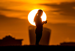 © Licensed to London News Pictures. 30/01/2018. London, UK. A jogger pauses to check her phone on the top of Primrose Hill as the sun rises. Photo credit: Peter Macdiarmid/LNP