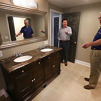 Wesley Jones, shows off the master bathroom of the home he remodeled and recently sold at 1157 West Jackson Street to Chris Rogers, a committee member of the NDC, during the West Jackson Street redevelopment ground breaking and tour Monday morning in Tupelo.