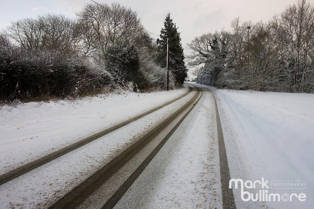 Photo: © Mark Bullimore..Winter Weather in the UK, Norfolk. Car tracks left in the snow on an isolated country road..07/01/2010