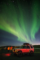 Photographers shooting the Northern Lights, next to a modified Land Rover Discovery 4x4. South Iceland