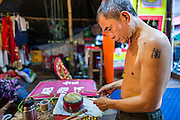 "19 AUGUST 2014 - BANGKOK, THAILAND:  A percussionist with the Lehigh Leng Kaitoung Opera troupe checks a small drum before a performance at Chaomae Thapthim Shrine, a small Chinese shrine in a working class neighborhood of Bangkok. The performance was for Ghost Month. Chinese opera was once very popular in Thailand, where it is called ""Ngiew."" It is usually performed in the Teochew language. Millions of Chinese emigrated to Thailand (then Siam) in the 18th and 19th centuries and brought their culture with them. Recently the popularity of ngiew has faded as people turn to performances of opera on DVD or movies. There are still as many 30 Chinese opera troupes left in Bangkok and its environs. They are especially busy during Chinese New Year and Chinese holiday when they travel from Chinese temple to Chinese temple performing on stages they put up in streets near the temple, sometimes sleeping on hammocks they sling under their stage. Most of the Chinese operas from Bangkok travel to Malaysia for Ghost Month, leaving just a few to perform in Bangkok.        PHOTO BY JACK KURTZ"