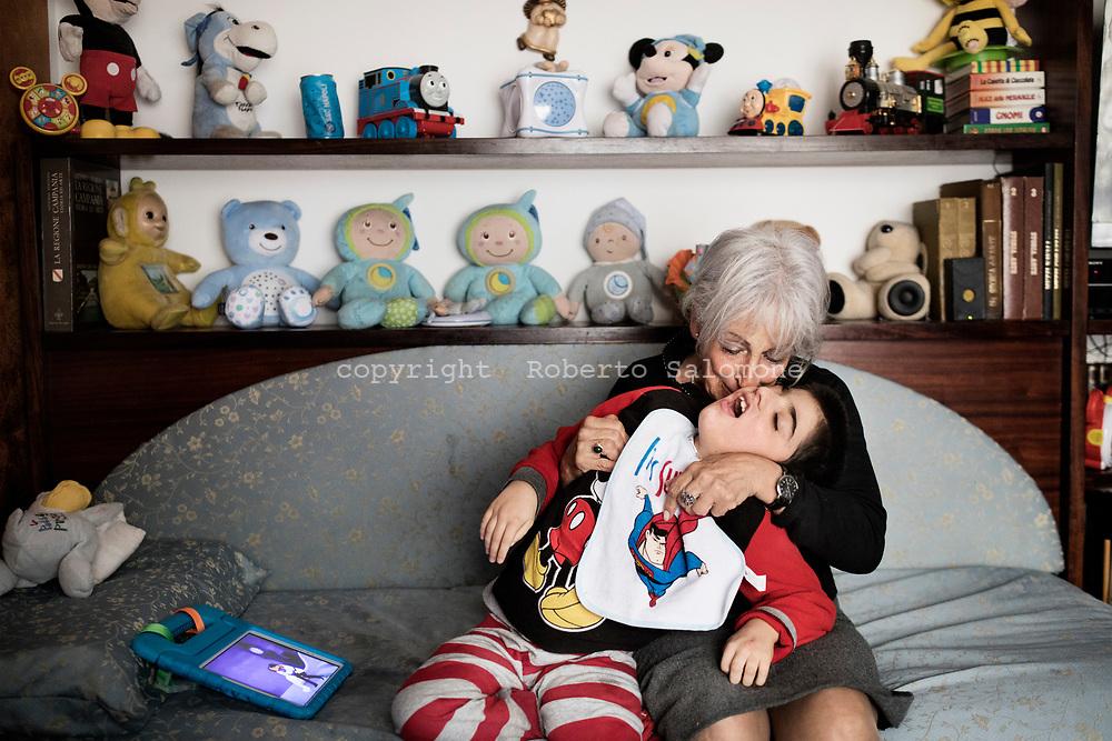 """Napoli, Italia - Rosalba e Francesco ritratti nella loro casa nel centro di Napoli. Francesco è un bambino disabile che Rosalba ha """"adottato"""" 8 anni fa. Rosalba si definisce anche una donna molto coraggiosa poichè anche i medici le avevano """"sconsigliato"""" di prendere in affidamento un bambino con problemi così gravi ad un'età non più giovanissima (71)."""
