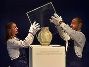 "© Licensed to London News Pictures. 28/09/2012. London, UK Auction room staff replace a protective box around A highly important Fatimid white-ground lustre pottery jar from Egypt dated 10th/11th century. The jar is expected to fetch 300,000-500,000GBP. Sotheby's Auction rooms in New Bond Street, London hold a photo call for their upcoming ""arts of the Islamic World"" auction which is expected to realise in the region of 5 million GBP . Photo credit : Stephen Simpson/LNP"