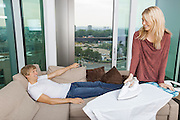Smiling woman looking at relaxed while ironing shirt in living room at home
