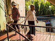 25 FEBRUARY 2015 - PHNOM PENH, CAMBODIA: Women pass each other in a stairwell of the White Building in Phnom Penh. The White Building, the first modern apartment building in Phnom Penh, originally had 468 apartments, and was opened the early 1960s. The project was overseen by Vann Molyvann, the first Cambodian architect educated in France. The building was abandoned during the Khmer Rouge occupation. After the Khmer Rouge were expelled from Phnom Penh in 1979, artists and dancers moved into the White Building. Now about 2,500 people, mostly urban and working poor, live in the building. Ownership of the building is in dispute. No single entity owns the building, some units are owned by their occupants, others units are owned by companies who lease out apartments. Many of the original apartments have been subdivided since the building opened and serve as homes to two or three families. The building has not been renovated since the early 1970s and is in disrepair. Phnom Penh officials have tried to evict the tenants and demolish the building but residents refuse to move out.    PHOTO BY JACK KURTZ