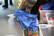 Astoria, New York<br /> March 30, 3016<br /> Kathy Vergara, 24, takes off her clown uniform after trying it on during a training she is leading at Blue Balloon Parties in Astoria, Queens on March 20, 2016.  She says she has a drastically different personality when inside her costume than out.  Vergara is also currently pregnant with twins.<br /> 3/30/16<br /> Tatiana Flowers/ CUNY Graduate School of Journalism)